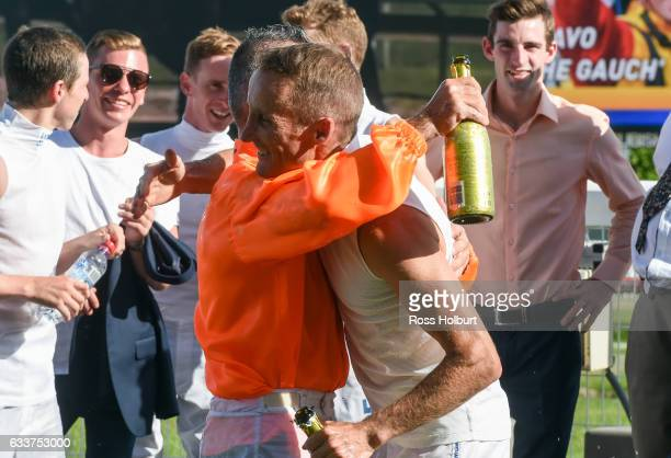 Damien Oliver toasts Darren Gauci after his farewell race at Caulfield Racecourse on February 04 2017 in Caulfield Australia