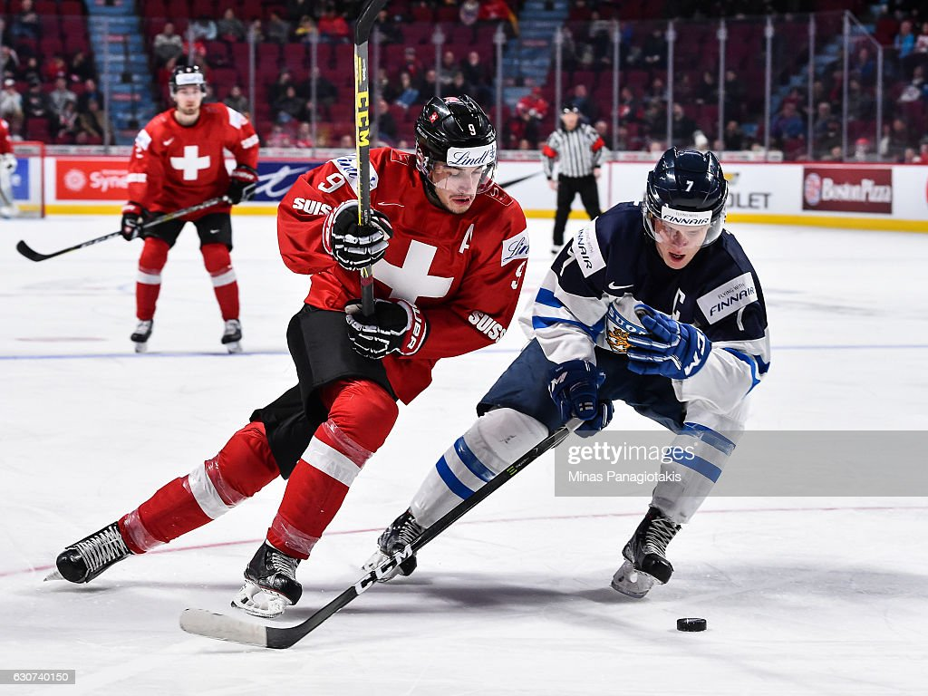 Damien Riat #9 of Team Switzerland and Olli Juolevi #7 of Team Finland chase the puck during the 2017 IIHF World Junior Championship preliminary round game at the Bell Centre on December 31, 2016 in Montreal, Quebec, Canada. Team Finland defeated Team Switzerland 2-0.