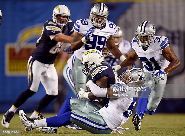 Damien Wilson of the Dallas Cowboys tackles Branden Oliver of the San Diego Chargers for a loss at Qualcomm Stadium on August 13 2015 in San Diego...