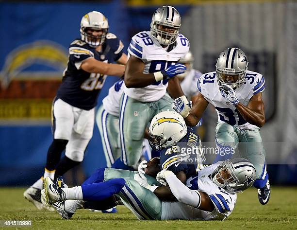 Damien Wilson of the Dallas Cowboys tackles Branden Oliver of the San Diego Chargers at Qualcomm Stadium on August 13 2015 in San Diego California