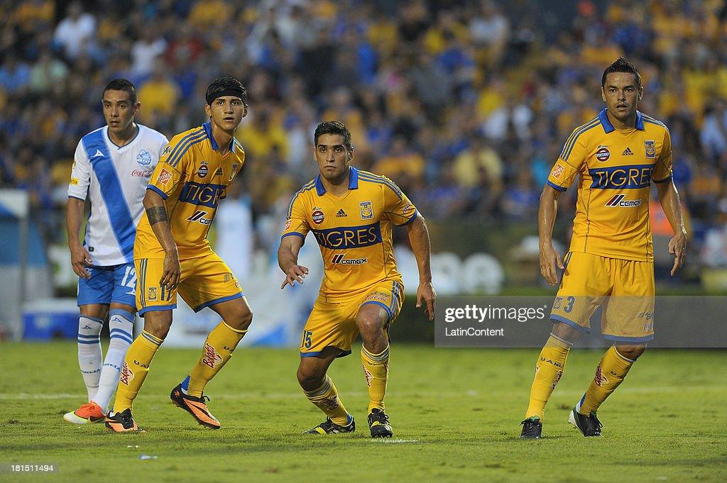 Damián Alvarez, Manuel Garcia and Juninho of Tigres in action during a match between Tigres UANL and Puebla FC as part of the Liga MX at Universitario stadium on September 21, 2013 in Monterrey, Mexico.