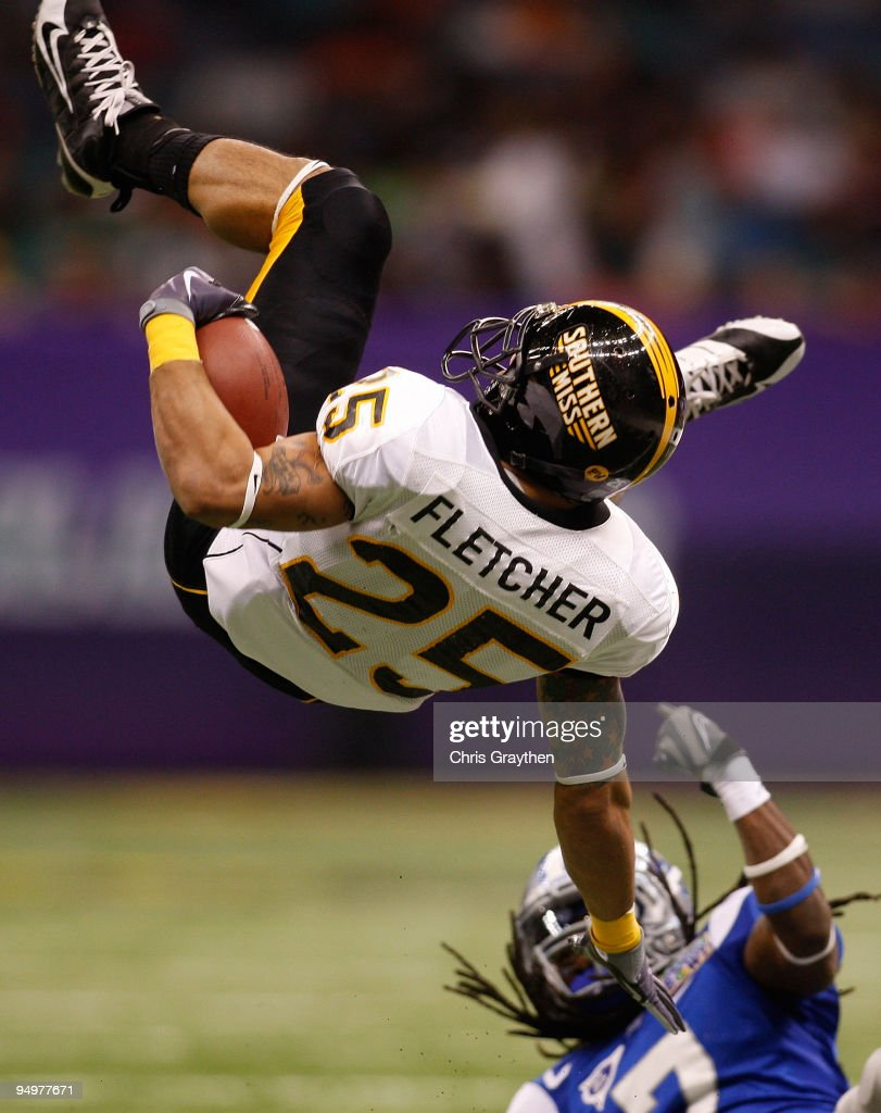 Damion Fletcher of the Southern Miss Golden Eagles is flipped upside down by Alex Suber of the Middle Tennessee Blue Raiders during the RL Carriers...