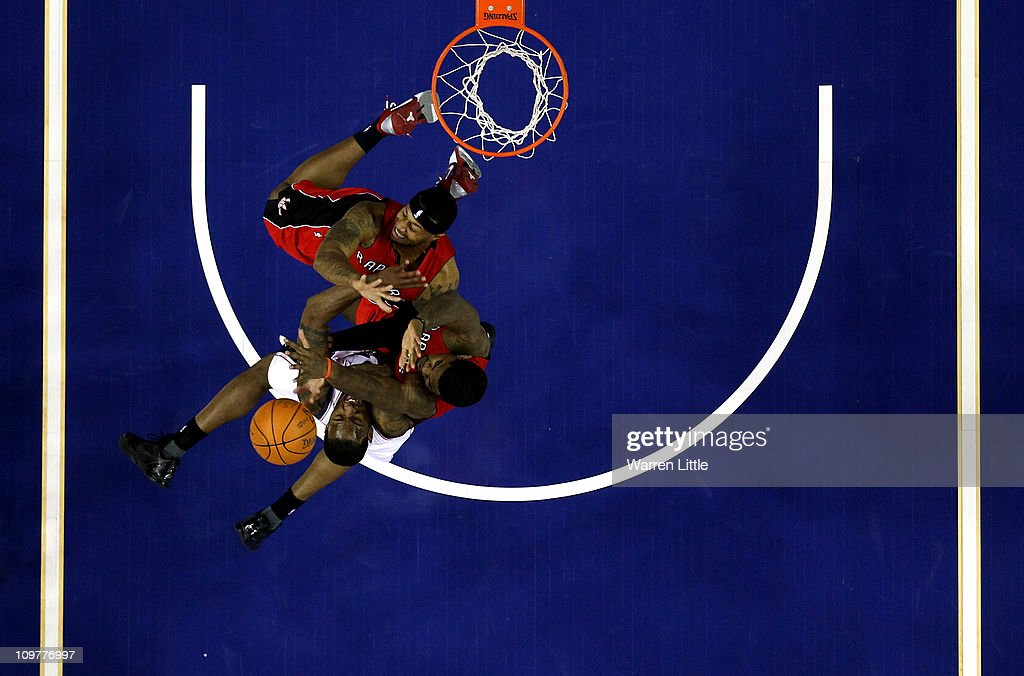 Damion James #10 of the Nets jumps against James Johnson #0 and Amir Johnson #15 of the Raptors during the NBA match between New Jersey Nets and the Toronto Raptors at the O2 Arena on March 4, 2011 in London, England.