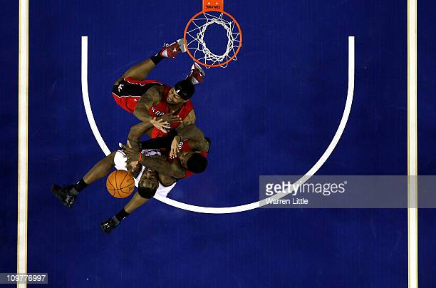 Damion James of the Nets jumps against James Johnson and Amir Johnson of the Raptors during the NBA match between New Jersey Nets and the Toronto...