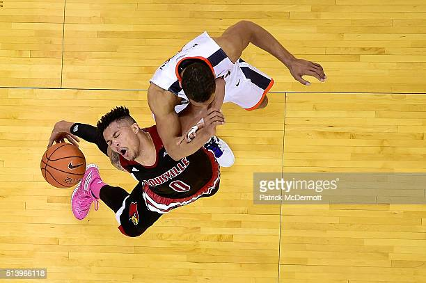 Damion Lee of the Louisville Cardinals dribbles the ball against Malcolm Brogdon of the Virginia Cavaliers in the second half during their game at...