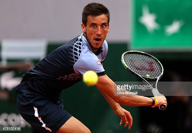Damir Dzumhur of Bosnia and Herzegovina returns a shot in his Men's Singles match against Roger Federer of Switzerland on day six of the 2015 French...