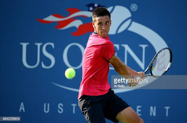 Damir Dzumhur of Bosnia and Herzegovina returns a shot to David Ferrer of Spain during his men's singles first round match on Day Two of the 2014 US...