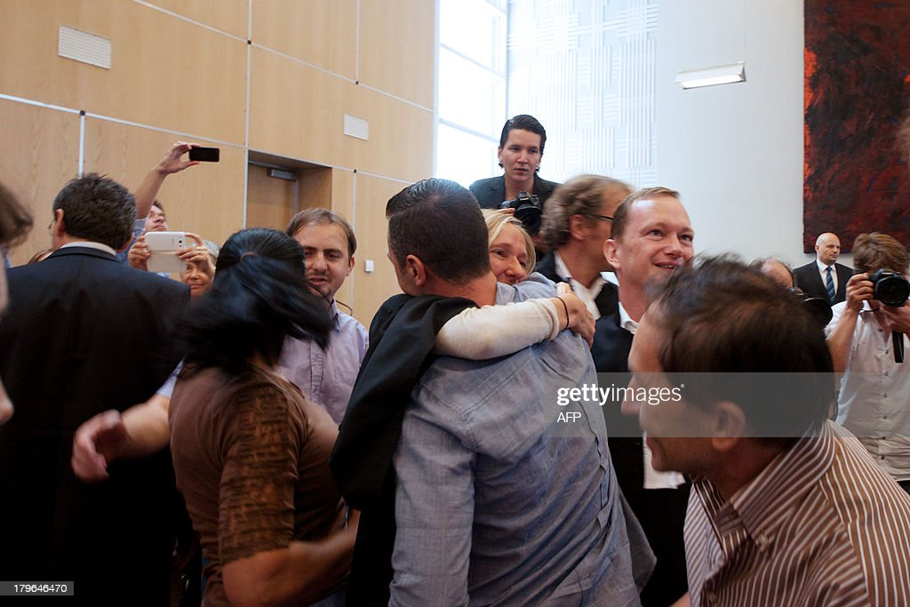 Damir Mustafic (C), the son of one of the victims, and his lawyer Liesbeth Zegveld embrace as they react to the ruling of the Supreme Court that the Netherlands is responsible for the deaths of three Muslim men after the fall of the Srebrenica enclave in 1995, on September 6, 2013 in The Hague. The Dutch state is responsible for sending three Bosnian Muslims to their deaths when they were expelled from a UN compound at Srebrenica in 1995, the supreme court ruled today. The final ruling in the long-running case means that former UN interpreter Hasan Nuhanovic, whose father, mother and brother were killed by Bosnian Serb forces after Dutch peacekeepers expelled them from the UN base, can seek compensation from the Dutch state. AFP PHOTO / NICOLAS DELAUNAY