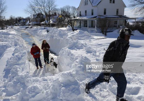 Damiyr Gallon right walks up a snow drift blocking Jefferson Blvd as Martha Pierce left and her daughter Kia Blum wait to climb with their mutts...
