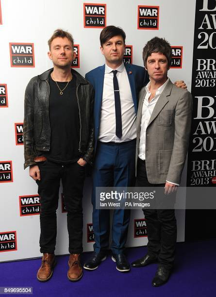 Damon Albarn and Noel Gallagher with Ben Knowles from War Child in the press room with a representative from charity War Child at the 2013 Brit...