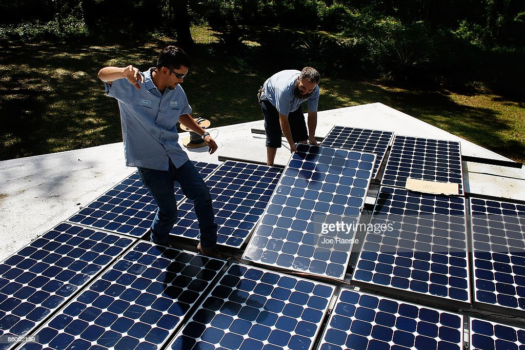 Damon Corkern (L) and Dustin Rodgers,who work for ECS Solar Energy Systems, Inc, install a solar panel system on the roof of a home on April 16, 2009 in Gainesville, Florida. Recently the city of Gainesville through a program initiated by the local Gainesville Regional Utilities became the first city in the nation to have a solar feed-in tariff ordinance which means owners of new solar photovoltaic systems will be eligible to receive 32 cents per kilowatt hour of electricity produced by the system over the next 20 years. The new program has produced a spurt of solar installation projects around the city. Other states and cities around the nation are eyeing the feed-in tariff program as a renewable energy program they might be interested in doing.