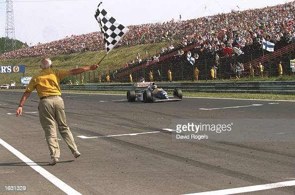 Damon Hill of Great Britain races past the chequered flag in his Williams Renault to win the Hungarian Grand Prix at the Hungaroring circuit in...