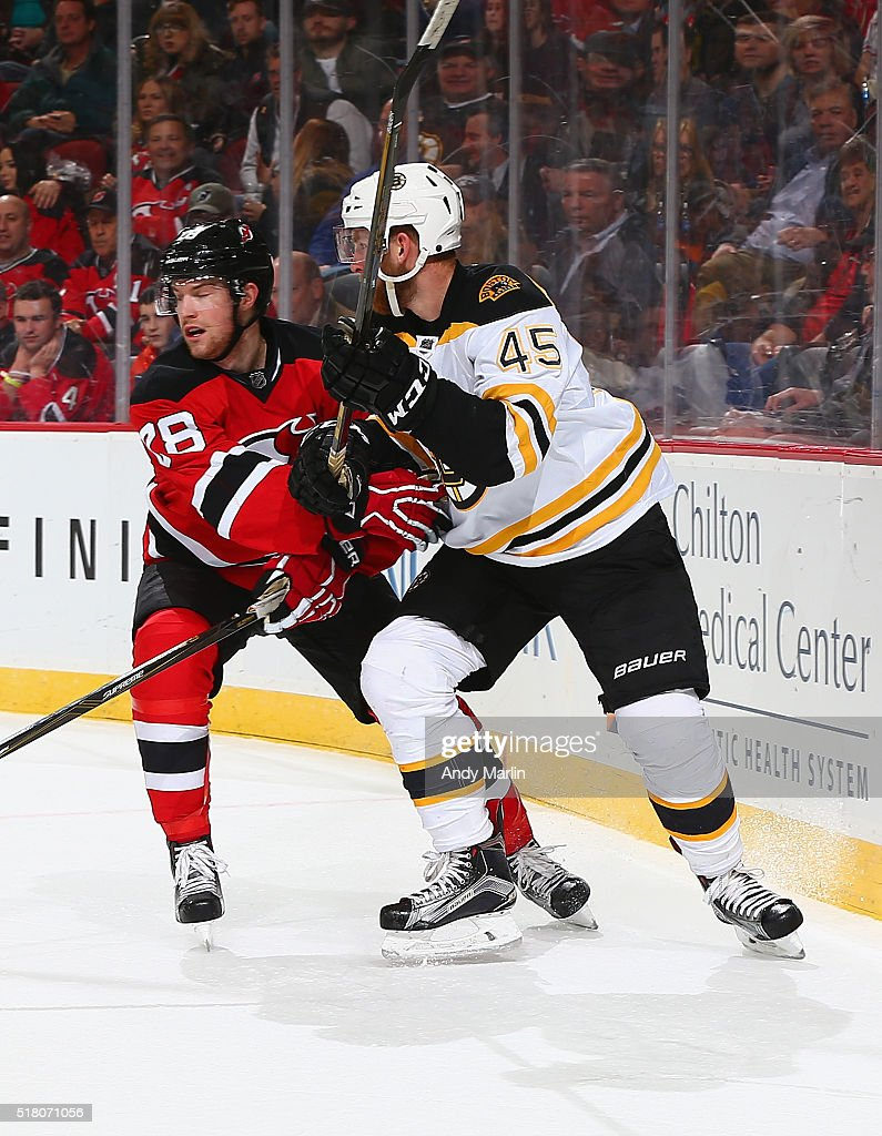 Damon Severson of the New Jersey Devils and Joe Morrow of the Boston Bruins battle for position during the game at the Prudential Center on March 29...
