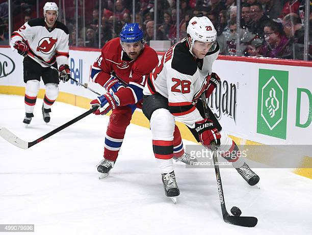 Damon Severson of the New Jersey Devils controls the puck while being challenged by Tomas Plekanec of the Montreal Canadiens in the NHL game at the...