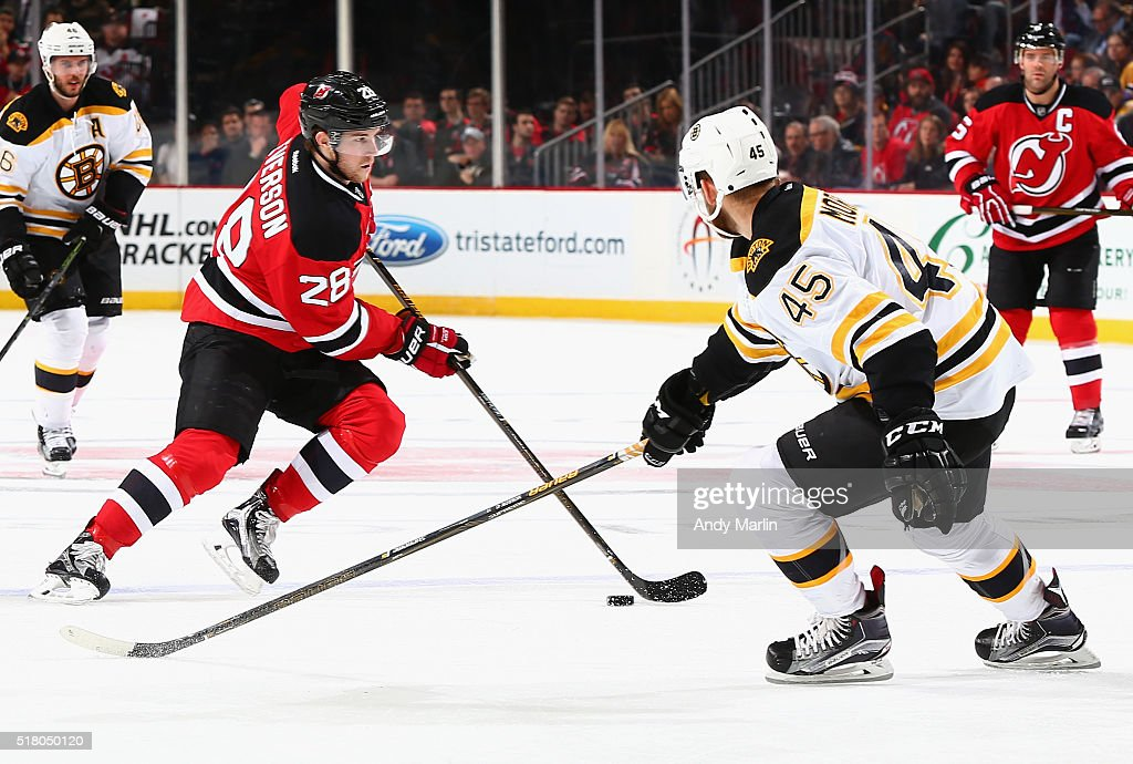 Damon Severson of the New Jersey Devils plays the puck away from Joe Morrow of the Boston Bruins during the game at the Prudential Center on March 29...