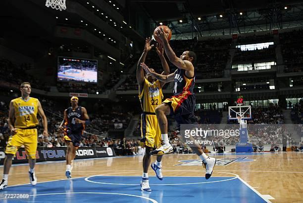 Damon Stoudamire of the Memphis Grizzlies shoots a layup past Larry Lewis of MMT Estudiantes during EA Sports NBA Europe Live Tour at Palacio de...