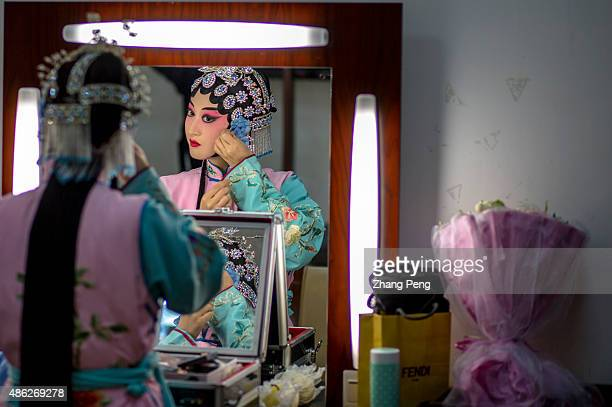Dan actress adds a decorating flower on her earside Every character in each opera has a unique makeup style Peking opera or Beijing opera is a form...