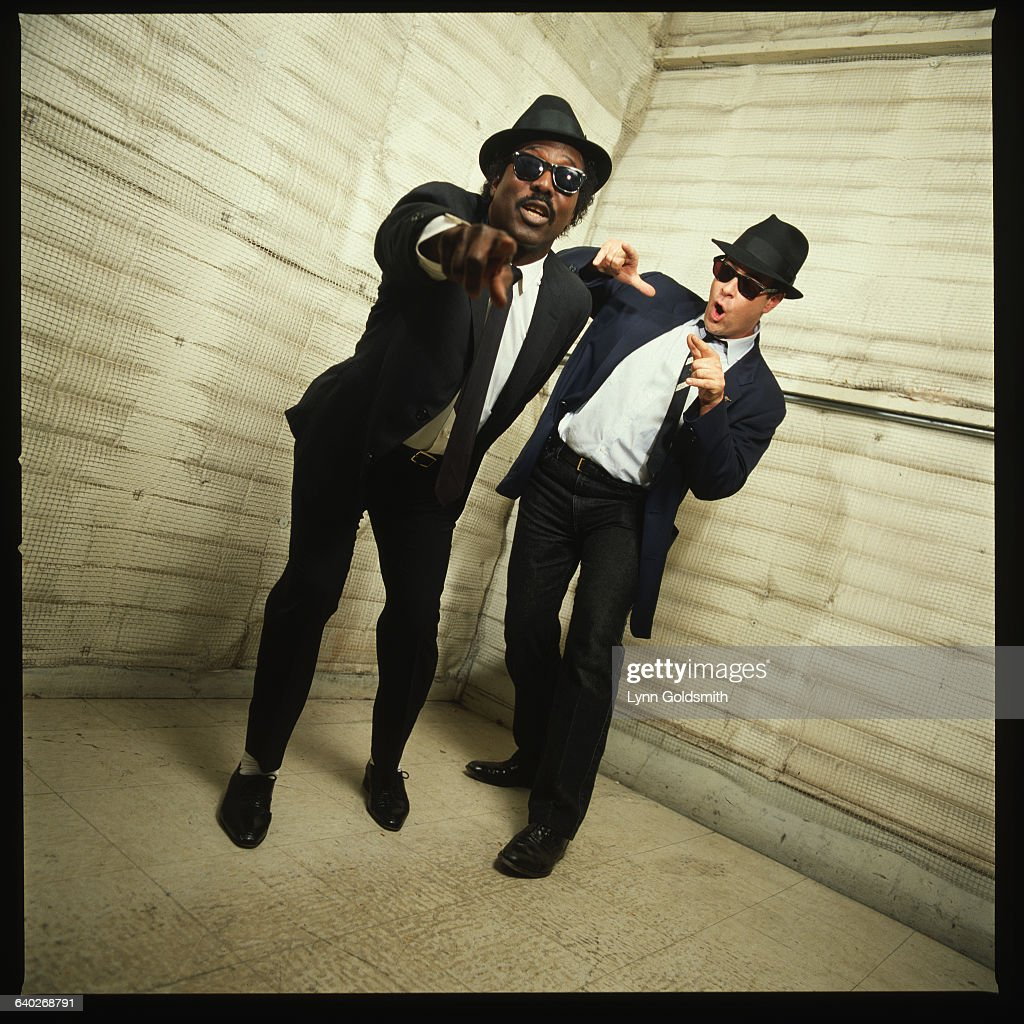 Dan Aykroyd, dressed as Elwood Blues from the movie The Blues Brothers, dances with singer Sam Moore.