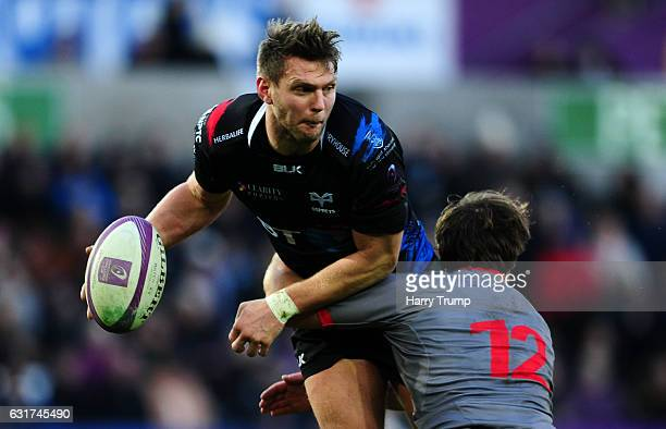 Dan Biggar of Ospreys is tackled by Theo Belan of Lyon during the European Rugby Challenge Cup match between Ospreys and Lyon at the Liberty Stadium...