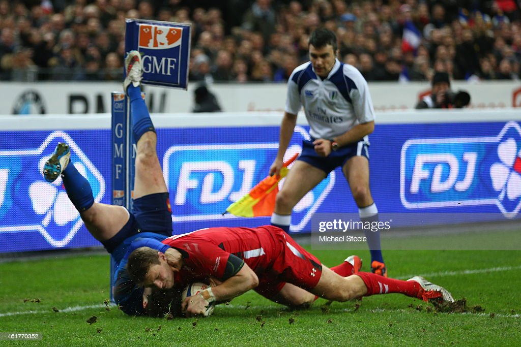 Dan Biggar of Wales scores his sides opening try despite the attention of Brice Dulin of France during the RBS Six Nations match between France and Wales at the Stade de France on February 28, 2015 in Paris, France.
