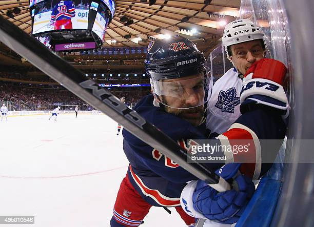 Dan Boyle of the New York Rangers rides Michael Grabner of the Toronto Maple Leafs into the boards during the first period at Madison Square Garden...