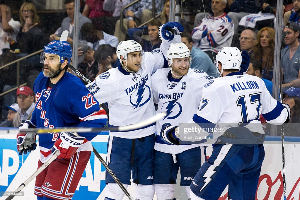 Dan Boyle of the New York Rangers skates away as Alex Killorn of the Tampa Bay Lightning is congratulated by his teammates Valtteri Filppula and...