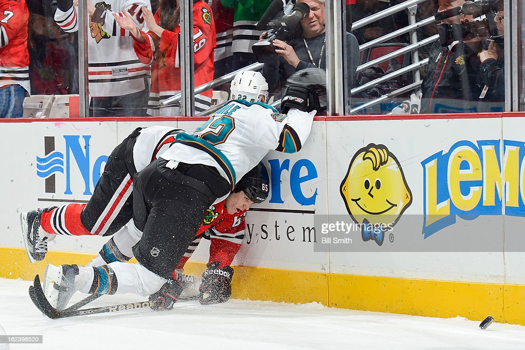 <a gi-track='captionPersonalityLinkClicked' href=/galleries/search?phrase=Dan+Boyle&family=editorial&specificpeople=201502 ng-click='$event.stopPropagation()'>Dan Boyle</a> #22 of the San Jose Sharks and Andrew Shaw #65 of the Chicago Blackhawks collide against the boards during the NHL game on February 22, 2013 at the United Center in Chicago, Illinois.