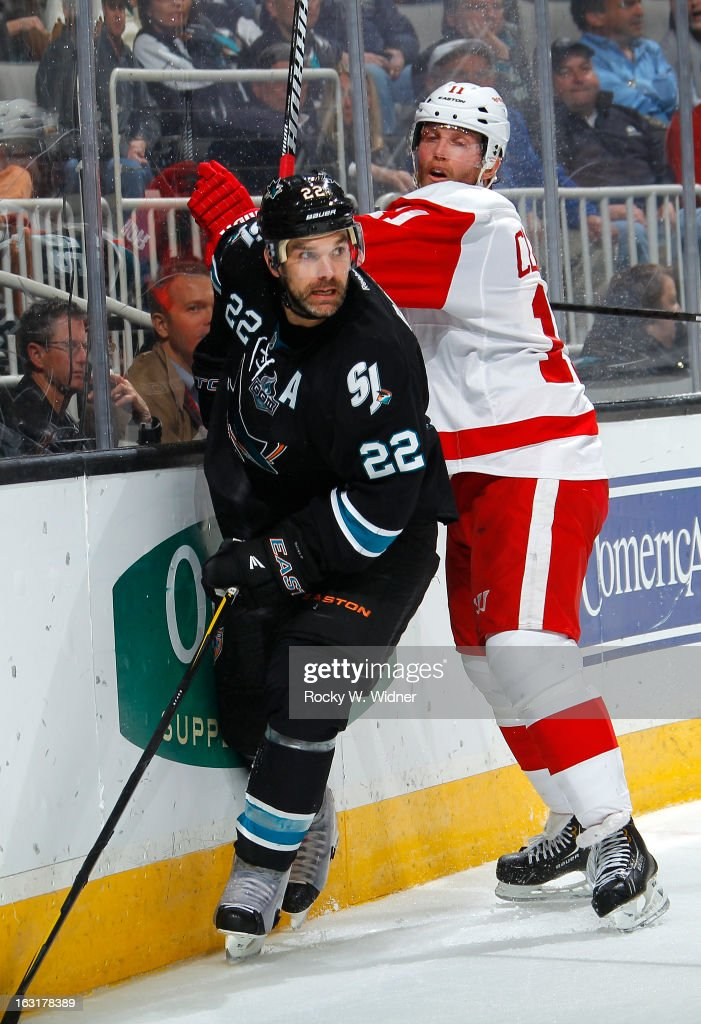 Dan Boyle of the San Jose Sharks and Daniel Cleary of the Detroit Red Wings battle for the puck at the HP Pavilion on February 26 2013 in San Jose...