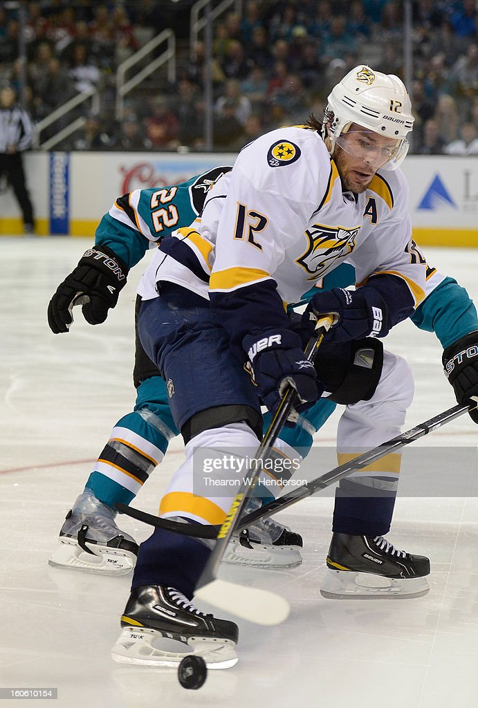 Dan Boyle #22 of the San Jose Sharks battle for control of the puck with Mike Fisher #12 of the Nashville Predators at HP Pavilion on February 2, 2013 in San Jose, California.