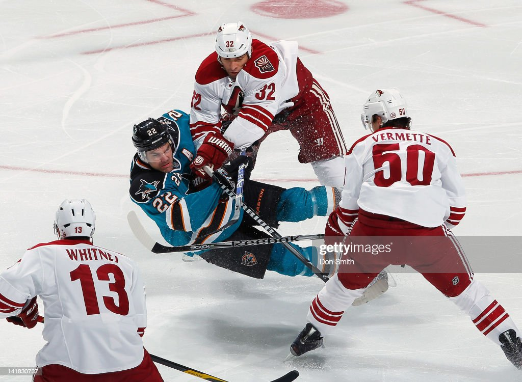 Dan Boyle of the San Jose Sharks takes a hit from Michal Rozsival of the Phoenix Coyotes as teammates Ray Whitney and Antoine Vermette look on at HP...