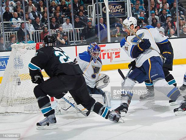 Dan Boyle of the San Jose Sharks takes a shot against Brian Elliott and Alex Pietrangelo of the St Louis Blues in Game Three of the Western...