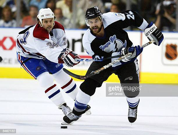Dan Boyle of the Tampa Bay Lightning skates up ice with the puck while being pursued by Jim Dowd of the Montreal Canadiens during Game one of the...