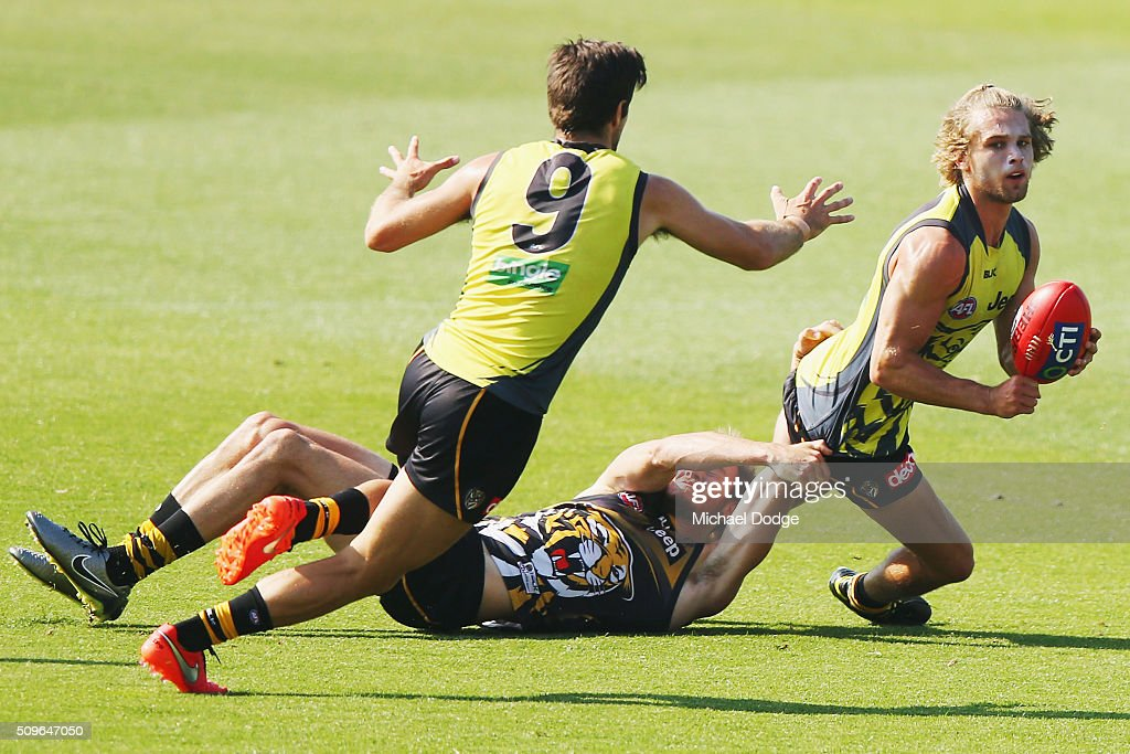 Dan Butler of the Tigers handballs to Trent Cotchin of the Tigers during the Richmond Tigers AFL intra-club match at Punt Road Oval on February 12, 2016 in Melbourne, Australia.
