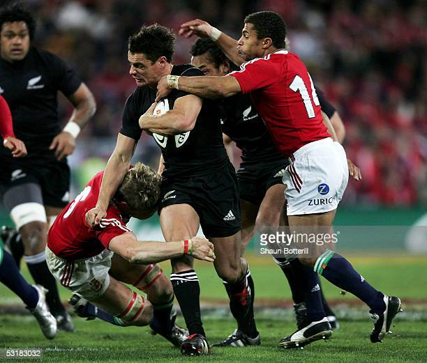 Dan Carter of the All Blacks is tackled by Simon Easterby and Jason Robinson of the Lions during the second test match between New Zealand All Blacks...
