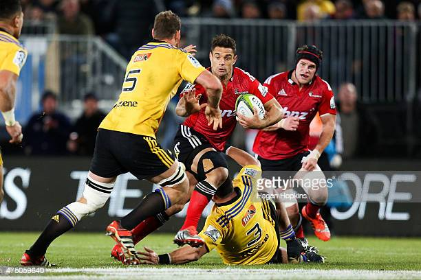 Dan Carter of the Crusaders is tackled by Jeffery ToomagaAllen and James Broadhurst of the Hurricanes during the round 16 Super Rugby match between...