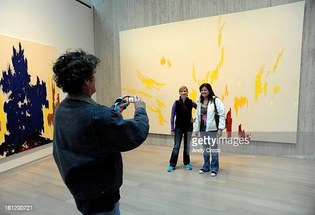 Dan Chapman left takes a picture of Resa Groff left and Molly O'Brien in front of a large painting by abstract expressionist artist Clyfford Still at...