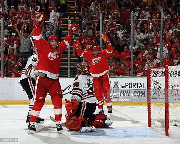 Dan Cleary and Marian Hossa of the Detroit Red Wings celebrate after Cleary's goal as goalie Cristobal Huet of the Chicago Blackhawks looks on during...