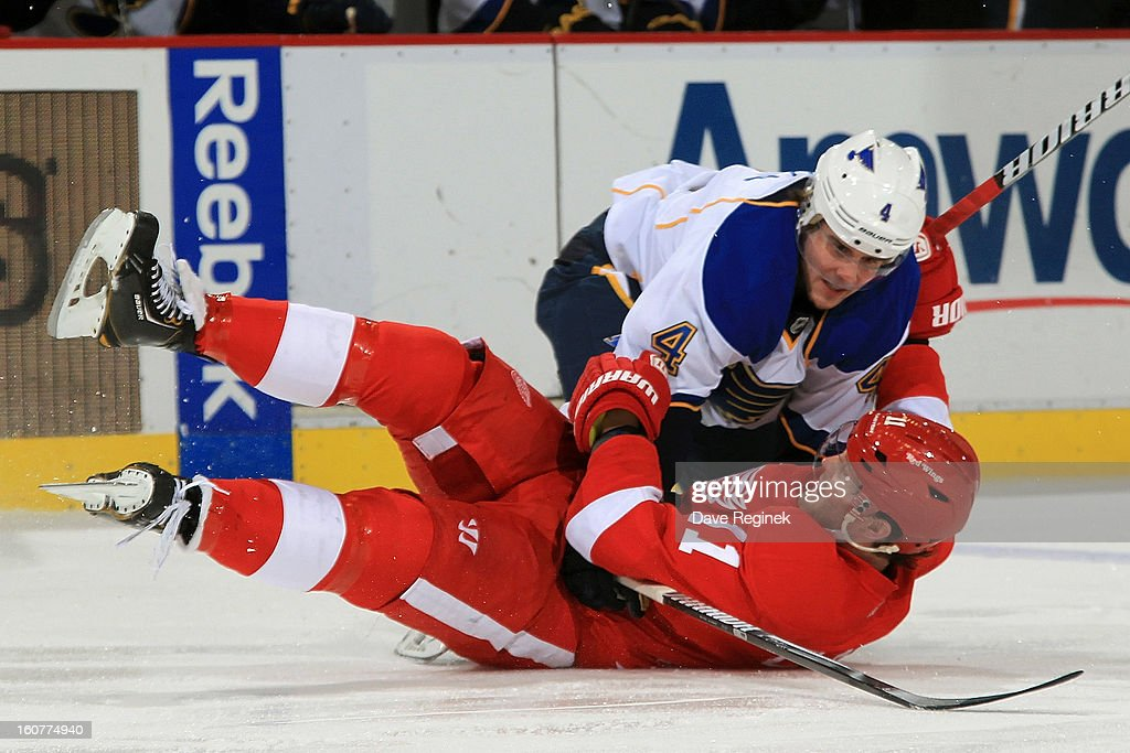 Dan Cleary of the Detroit Red Wings is checked to the ice by Kris Russell of the St Louis Blues during a NHL game at Joe Louis Arena on February 1...
