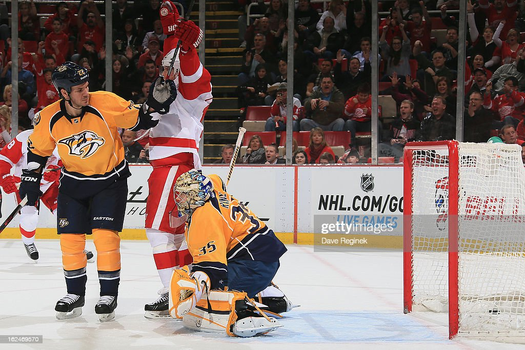 Dan Cleary of the Detroit Red Wings raises his arms on teammate Niklas Kronwall's second period goal as Pikka Rinne and Scott Hannan of the Nashville...