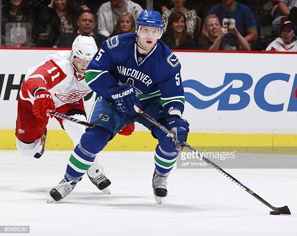 Dan Cleary of the Detroit Red Wings tries to check Christian Ehrhoff of the Vancouver Canucks as he skates up ice during their game at General Motors...