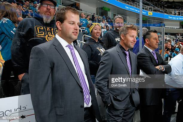 Dan Darrow Johan Hedberg and Bob Boughner of the San Jose Sharks coaching staff look out over the ice during warm ups wearing their lavender ties...