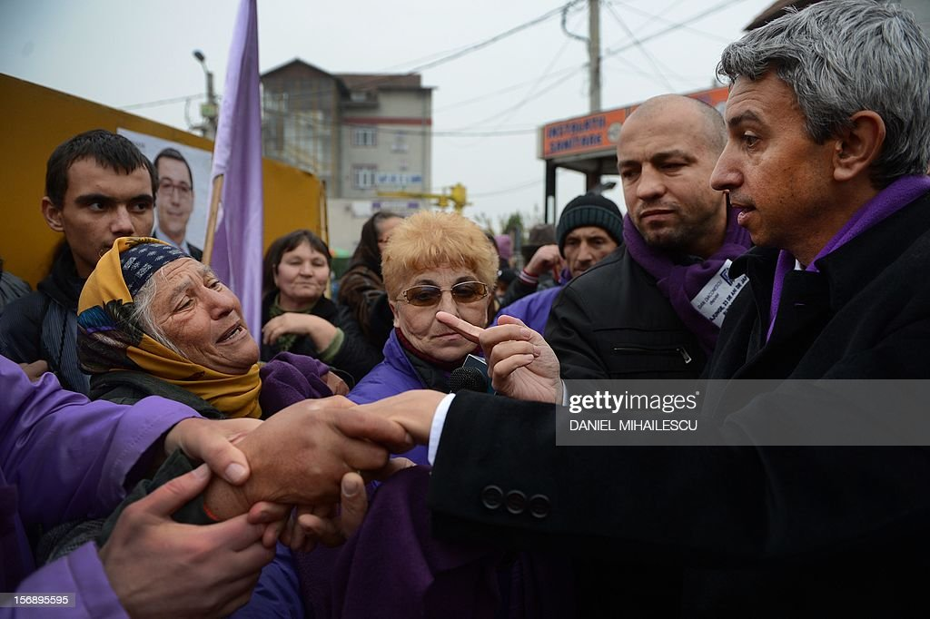 Dan Diaconescu (R) the president of Dan Diaconescu Popular Party (PP-DD) shakes hands with supporters during an electoral meeting in Targu Jiu city (300km west from Bucharest) November 23, 2012. Famous for its enticing emissions, the head of the private channel OTV plans gain the presidency in 2014. Romanians are called to ballots on December 9, 2012 for the parliamentary elections. AFP PHOTO DANIEL MIHAILESCU