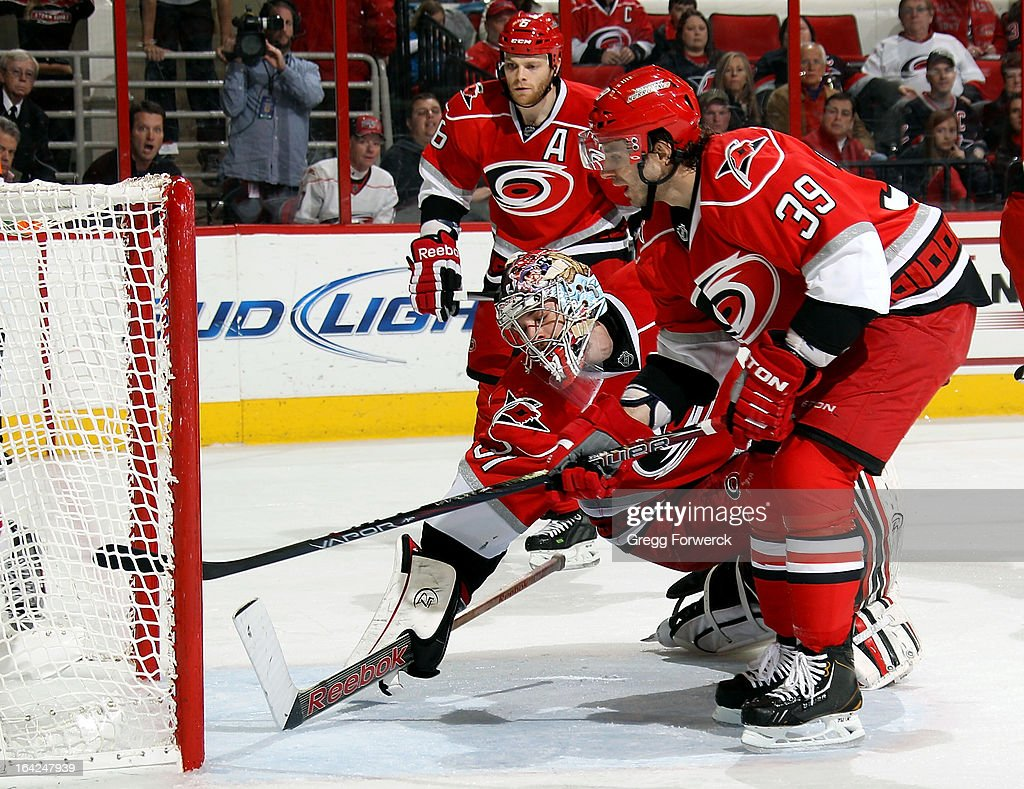 Dan Ellis #31 of the Carolina Hurricanes lunges toward the net behind Patrick Dwyer #39 in an failed effort to prevent a goal scored by Adam Henrique of the New Jersey Devils as Tim Gleason #6 looks on during their NHL game at PNC Arena on March 21, 2013 in Raleigh, North Carolina.