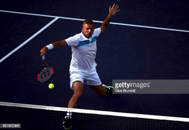Dan Evans of Great Britain plays a backhand volley against Dustin Brown of Germany in their first round match during day five of the BNP Paribas Open...