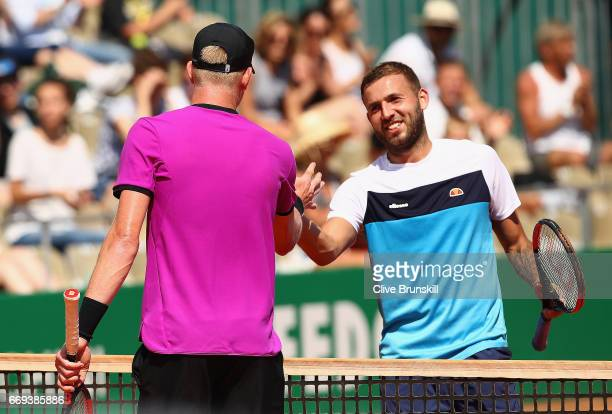 Dan Evans of Great Britain shakes hands at the net after his straight sets defeat by Kyle Edmund of Great Britain in their first round match on day...