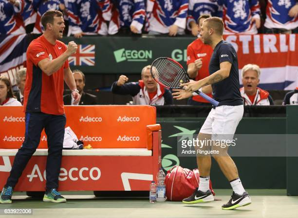 Dan Evans of Great Britain shakes hands with team captain Leon Smith after winning a point in the tiebreaker of the first set in his singles match...