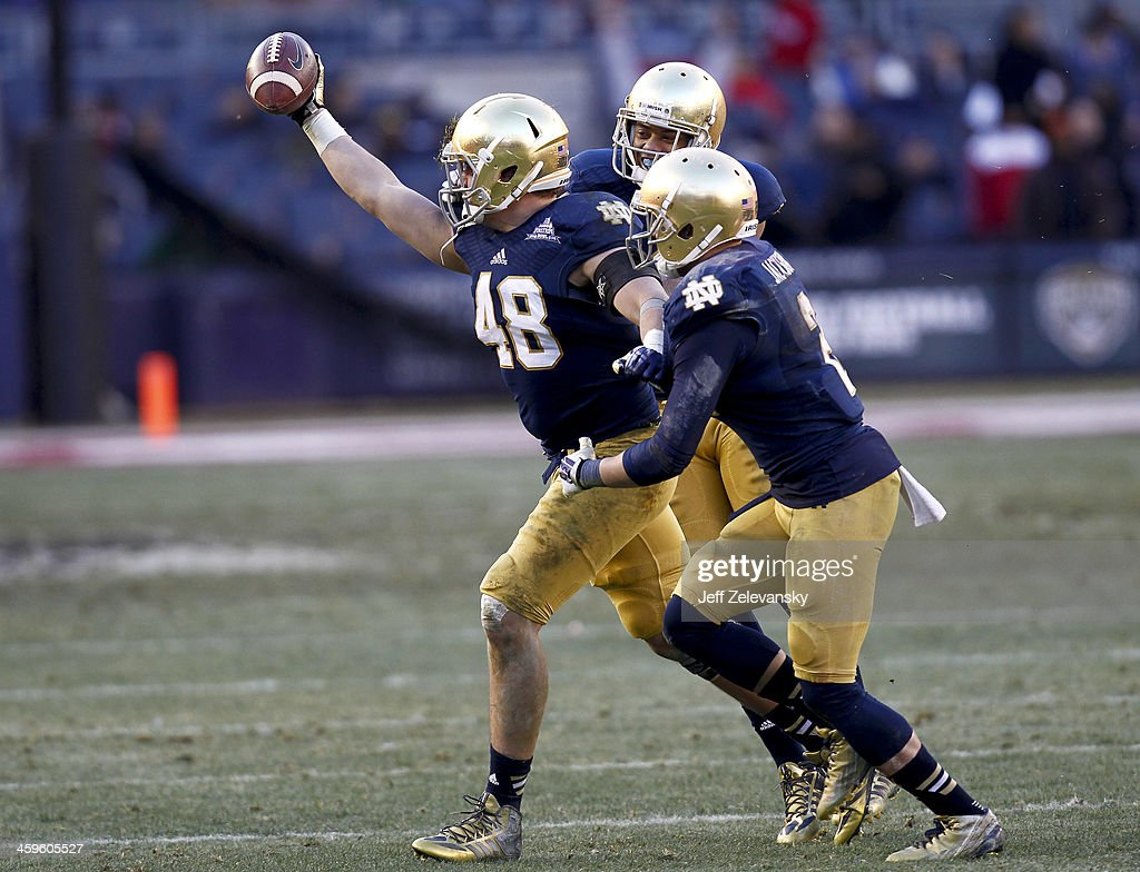 Dan Fox #48 of the Notre Dame Fighting Irish celebrates an interception against the Rutgers Scarlet Knights during the New Era Pinstripe Bowl at Yankee Stadium on December 28, 2013 in the Bronx borough of New York City.