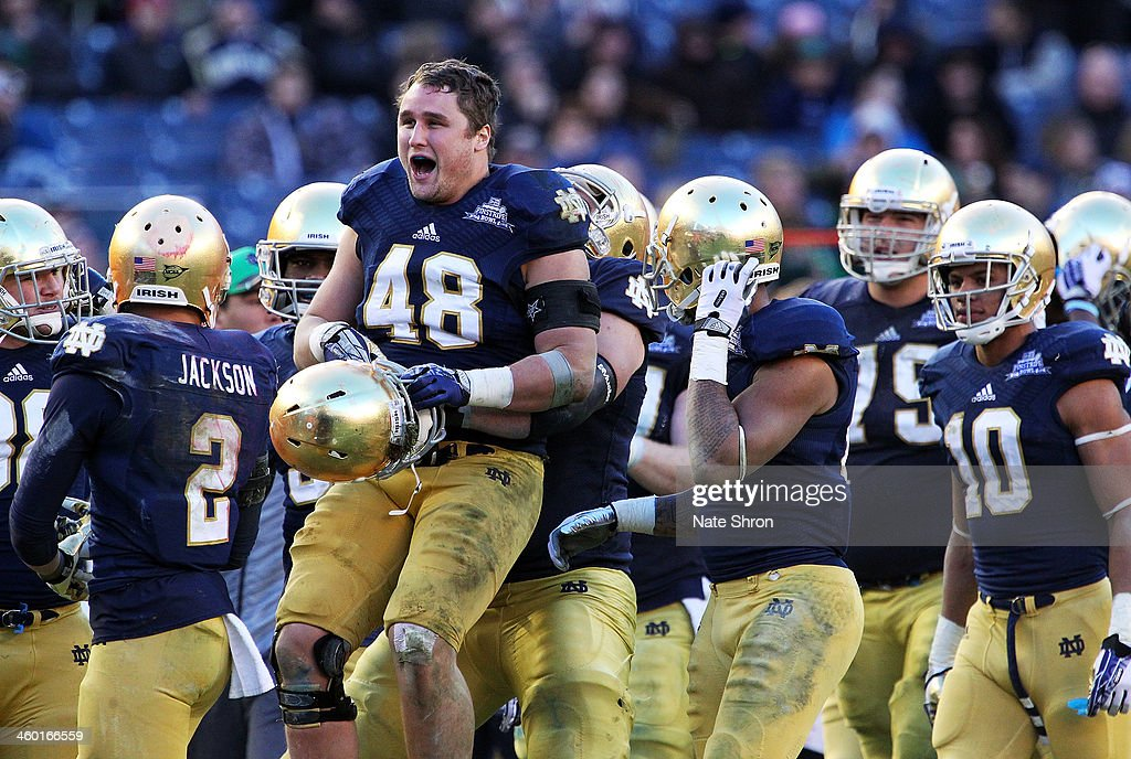 Dan Fox #48 of the Notre Dame Fighting Irish smiles as he is lifted up by teamates in celebration after a play against the Rutgers Scarlet Knights during the New Era Pinstripe Bowl at Yankee Stadium on December 28, 2013 in the Bronx Borough of New York City.