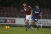 Dan Gardner of Chesterfield plays the ball watched by Ben Tozer of Northampton Town during the Sky Bet League Two match between Northampton Town and...