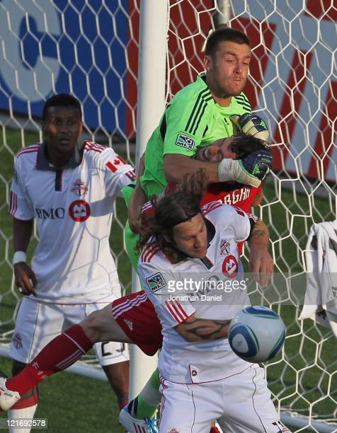 Dan Gargan of the Chicago Fire gets caught between goalkeeper Milos Kocic and Torsten Frings of Toronto FC as Danleigh Borman stands in the goal...